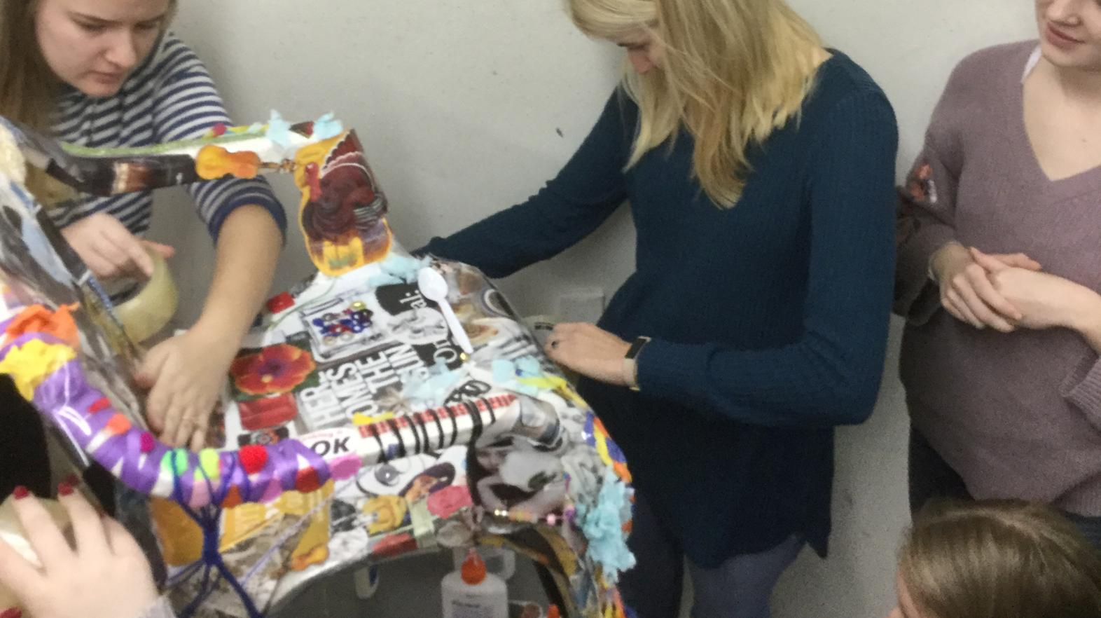 Art therapy students work together on a chair.
