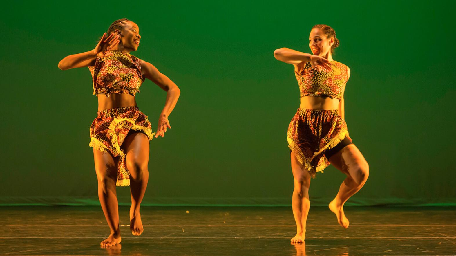 Two dancers perform an African Dance piece on stage
