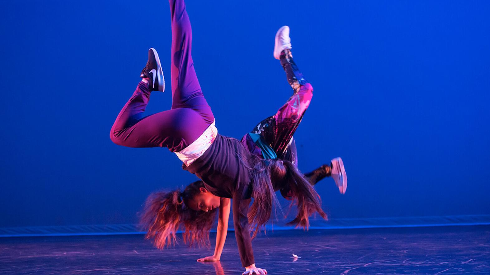 Two dancers perform a hip hop routine