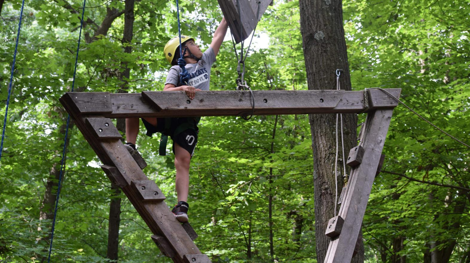 A camper climbs the rope course.