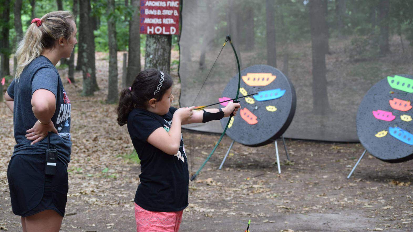 Camper shoots a bow and arrow.