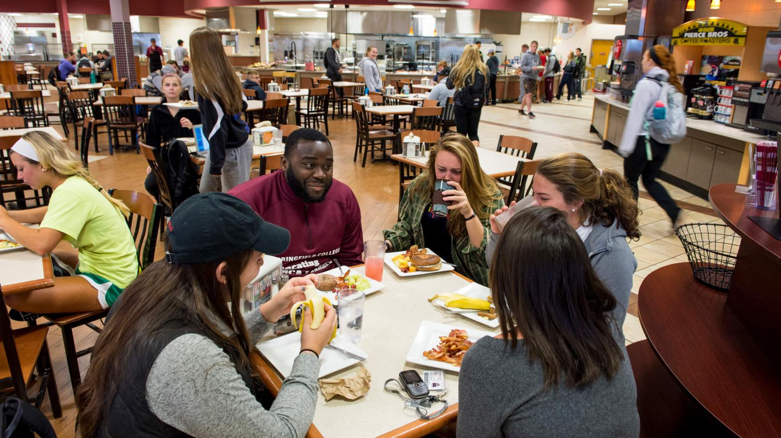Students sit at a table and eat in Cheney Cafeteria.