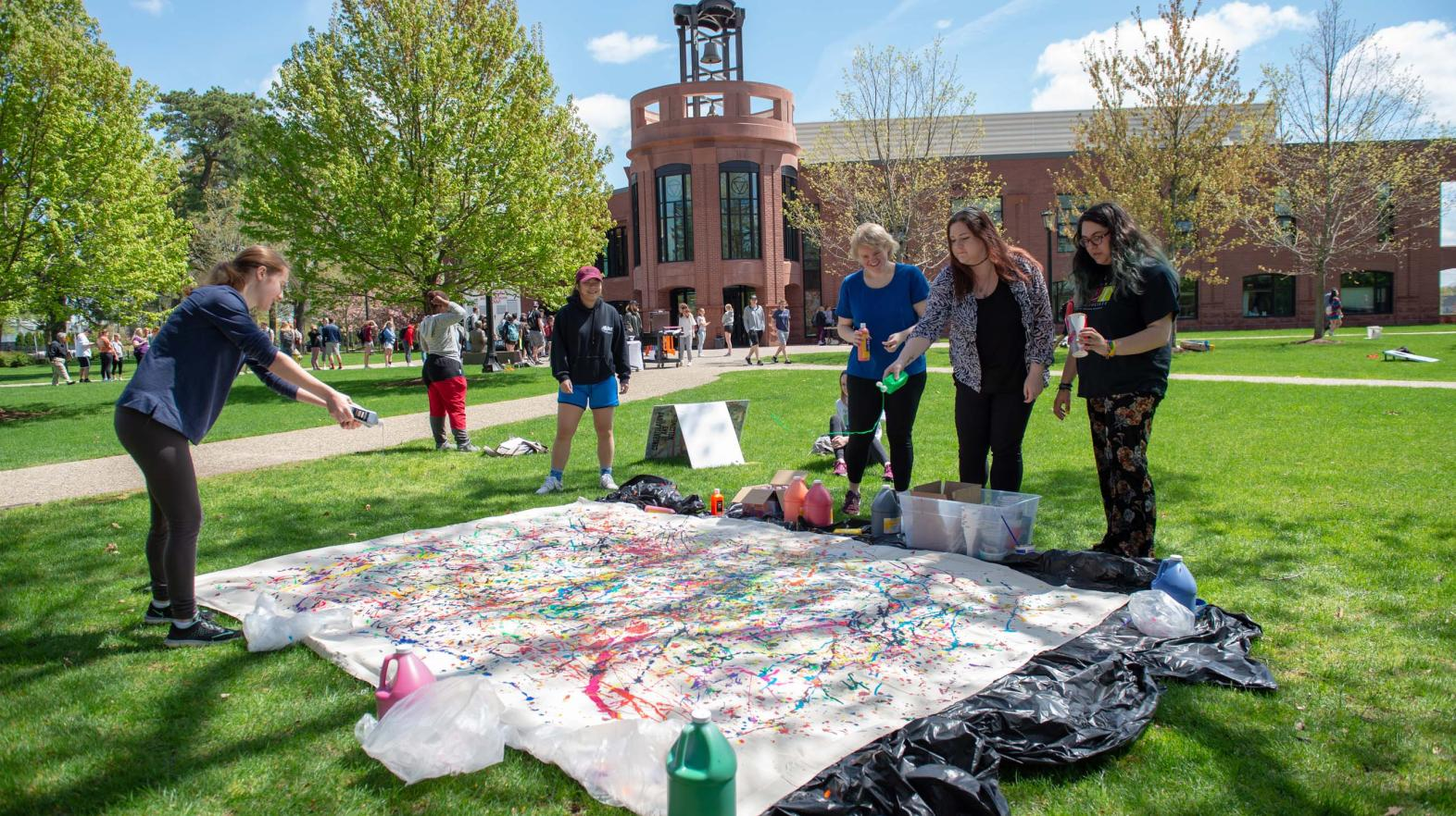 Students throw paint on a tarp on the quad.