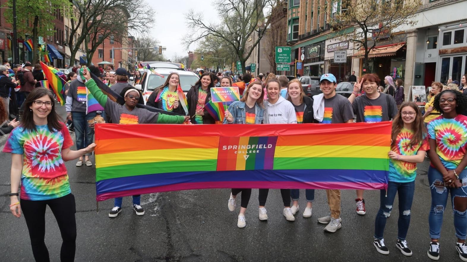 Students march with a rainbow Springfield College sign at a Pride Parade.