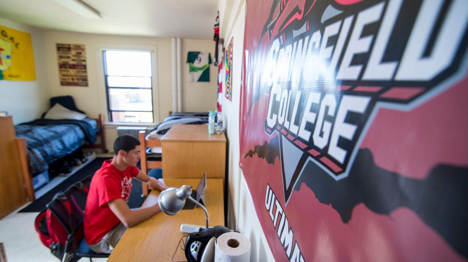 A student sits on his computer in one the residence halls.