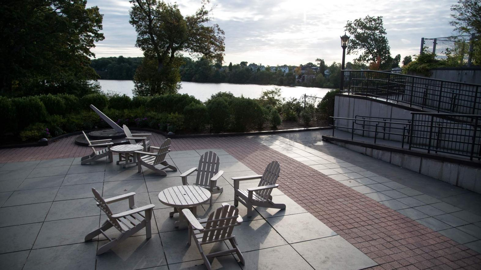 A view with chairs and tables overlooking Lake Massasoit.