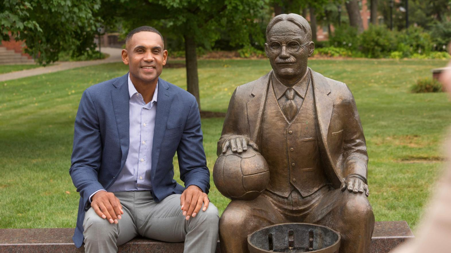 Grant Hill sits next to the James Naismith statue.