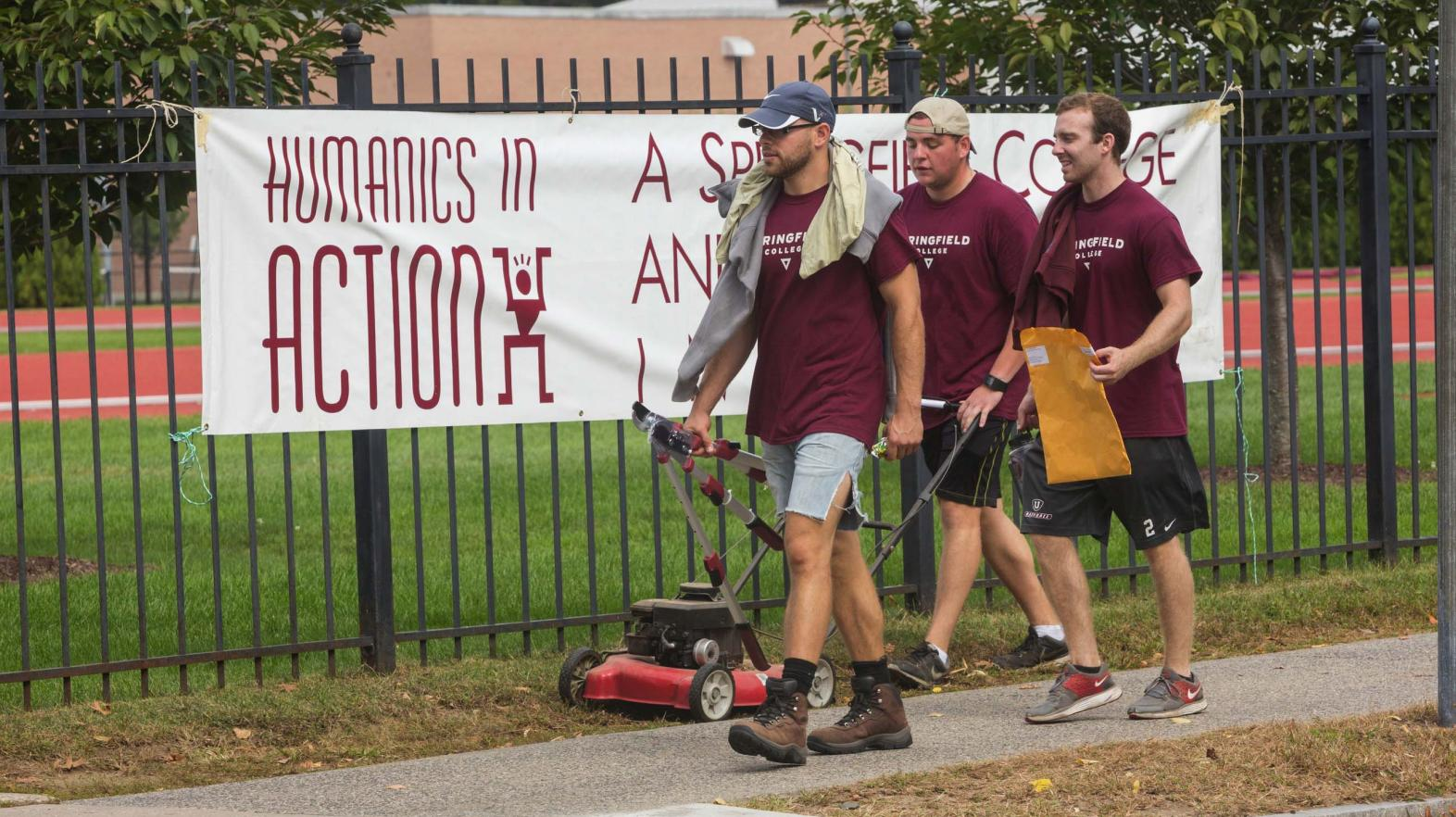 Students carry yard work supplies past a Humanics in Action day sign.