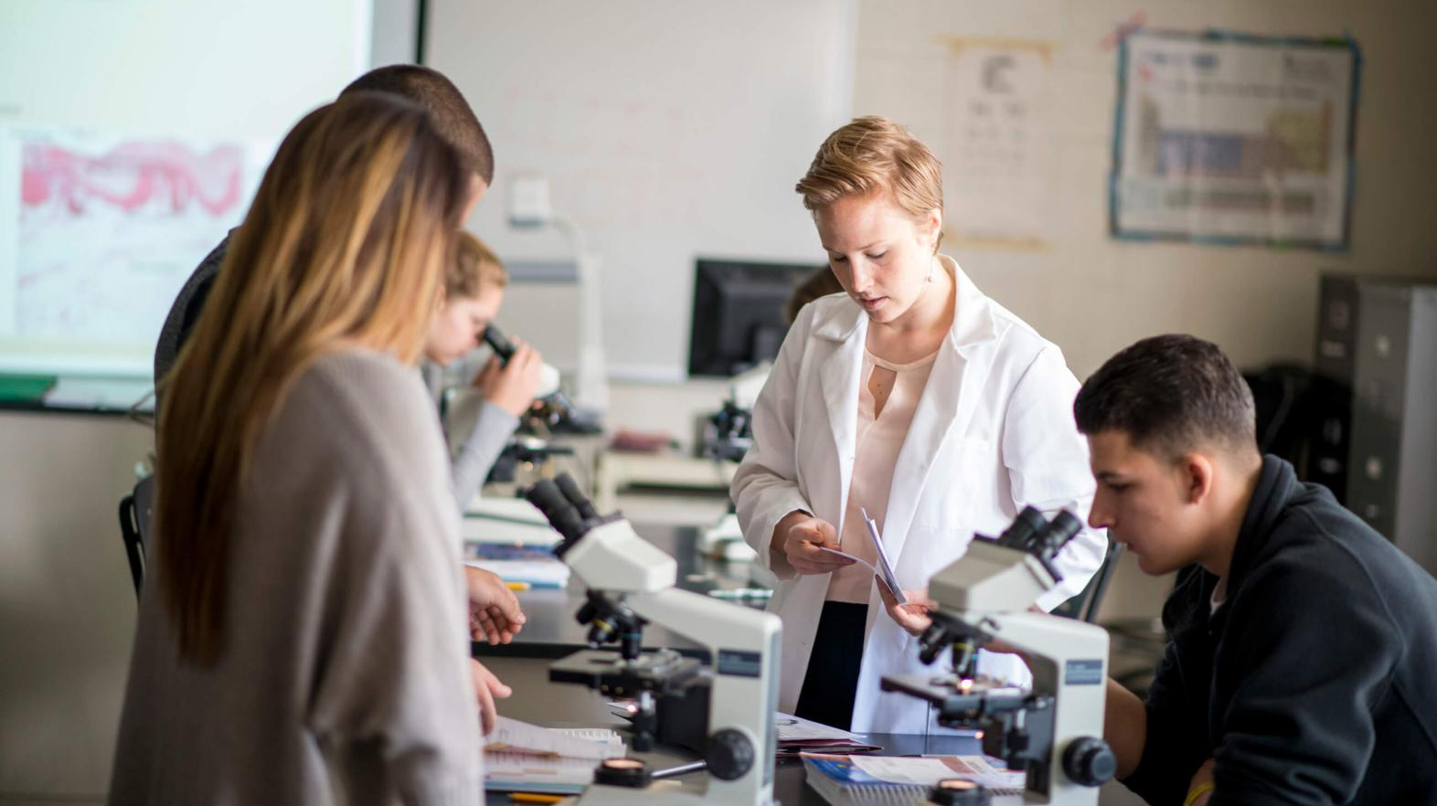 A professor works with her students and microscopes.