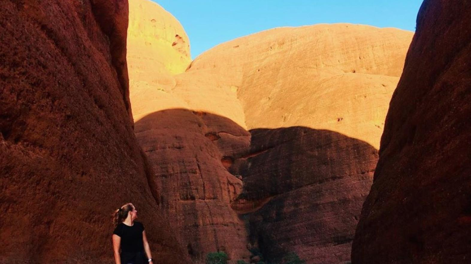 A study abroad student stands in front of a canyon.