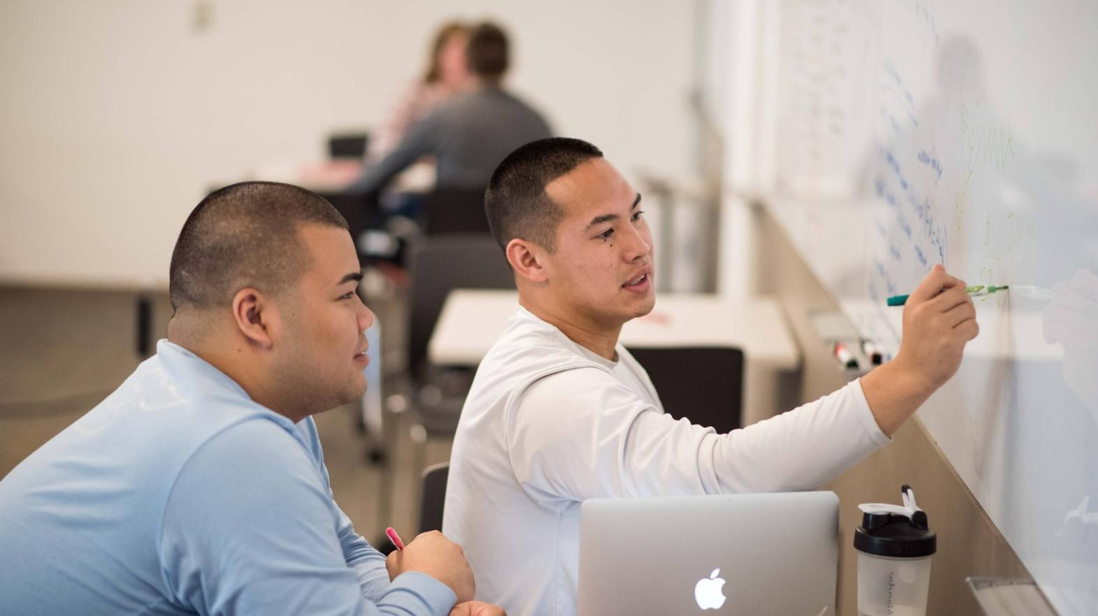 Two students use the white board in the academic success center.