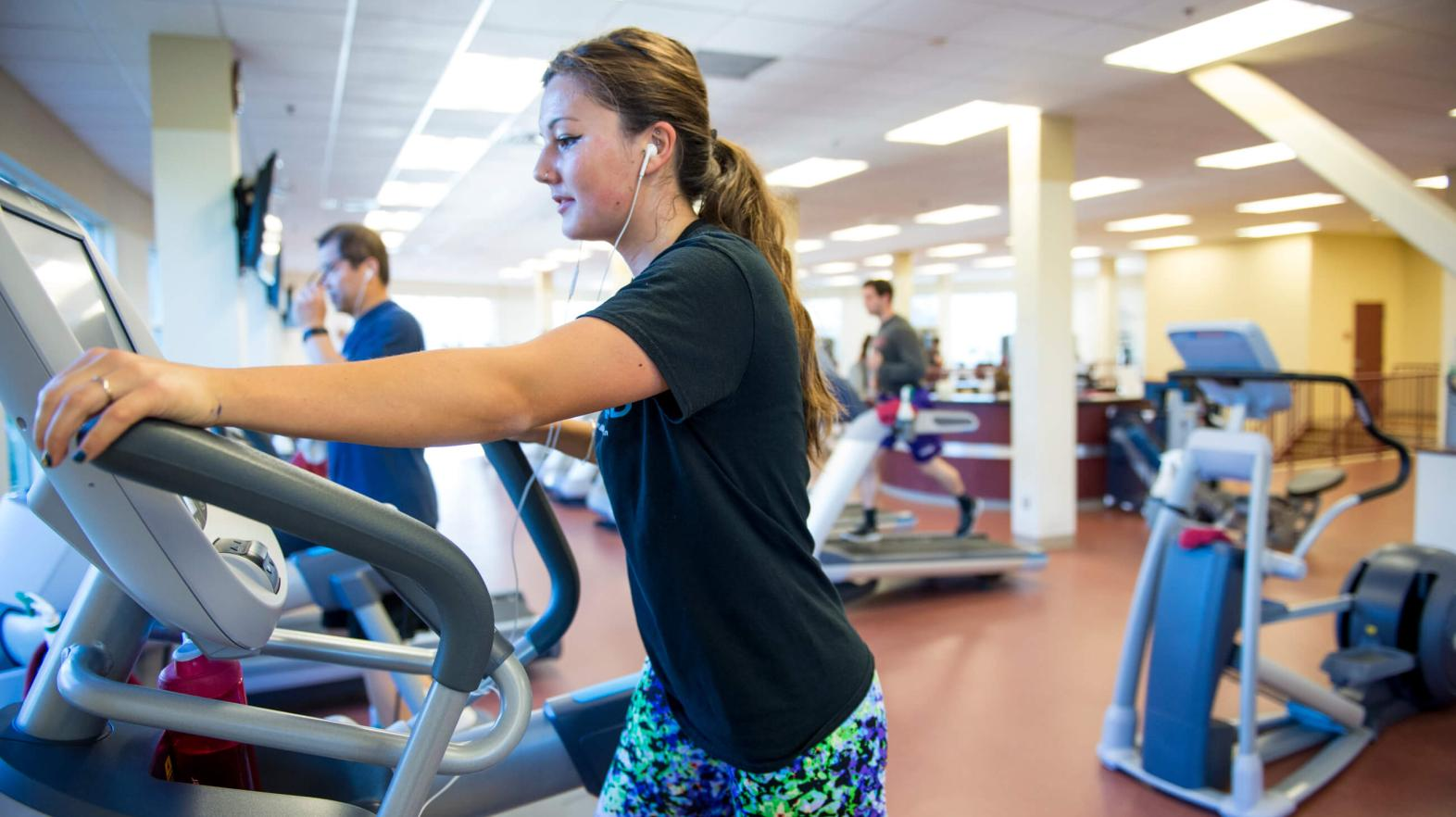 A young woman works out on an elliptical.