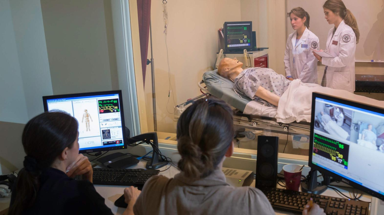 Two students observe two other students who are in the simulation lab.