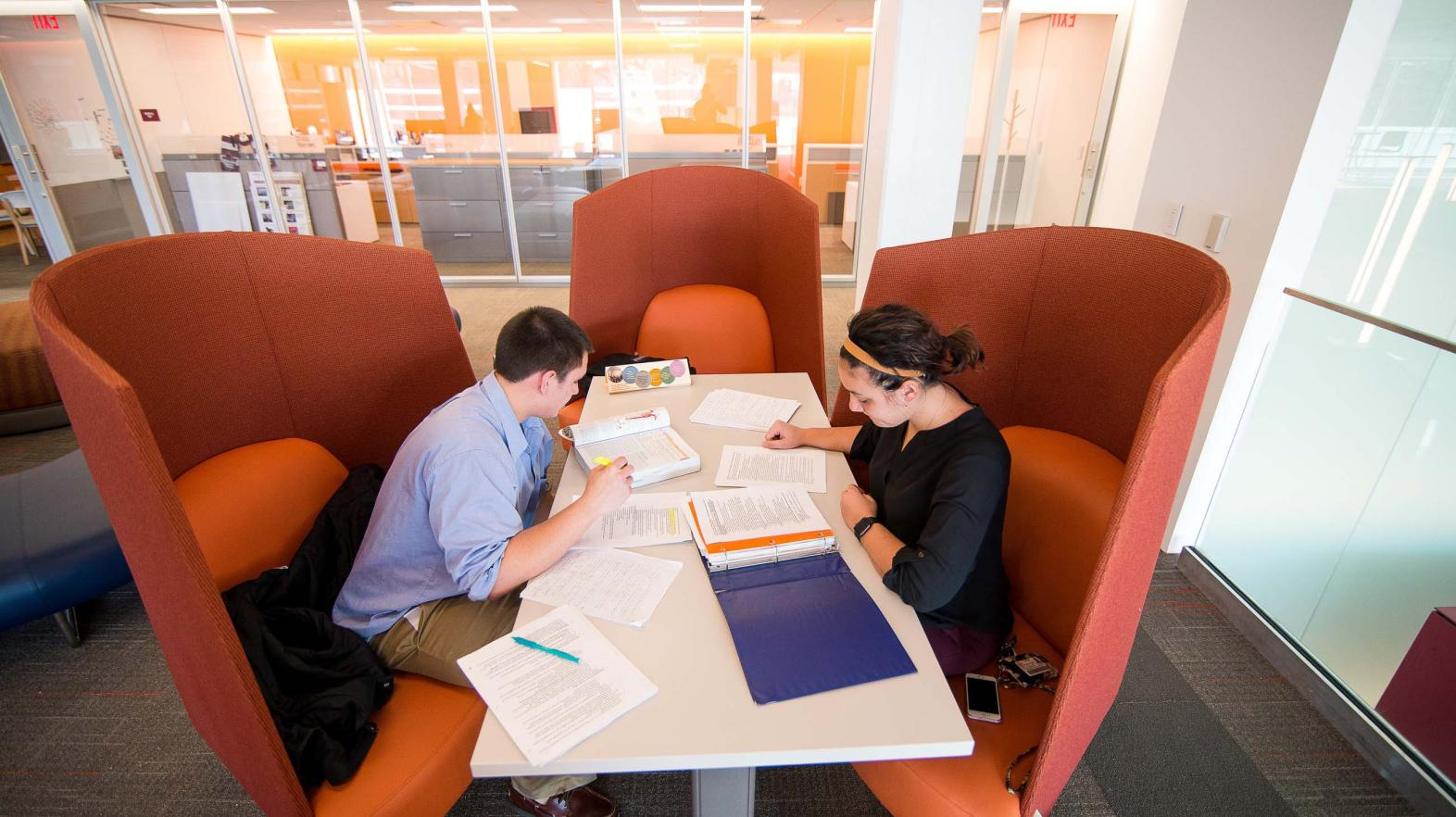 Two students sit at a table in the Learning commons, studying.