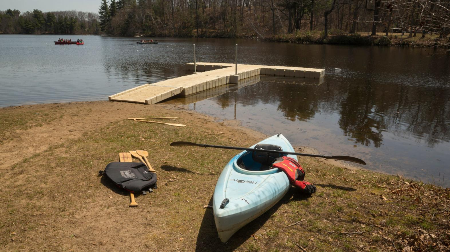 A kayak sits near the dock on the shores of Lake Massasoit