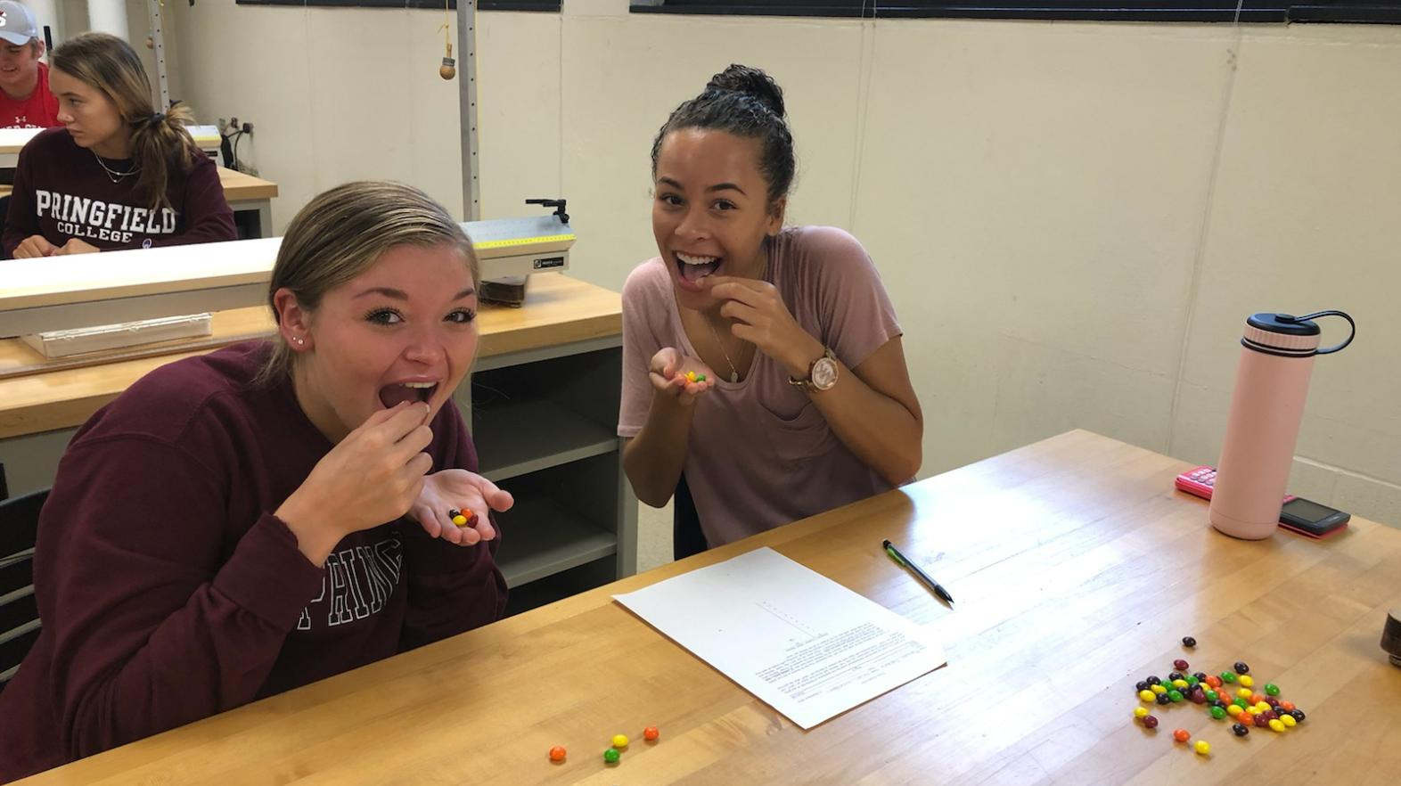 Two female students pretend to eat skittles during a math assignment
