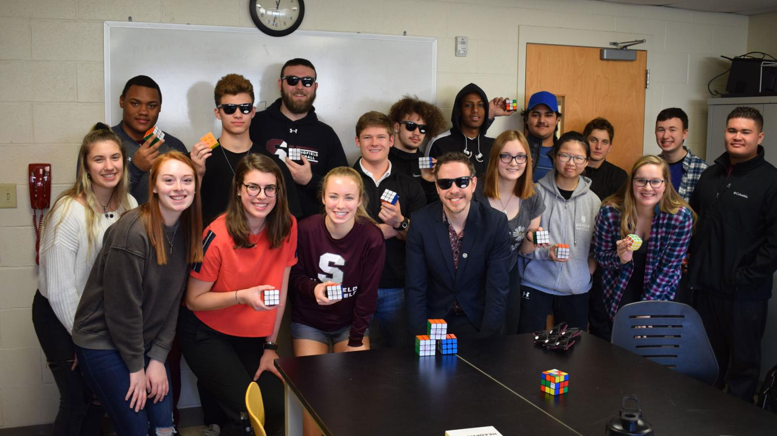 A group of students from the Springfield College Department of Mathematics, Physics, and Computer Science stand together at a Rubik's Cube competition