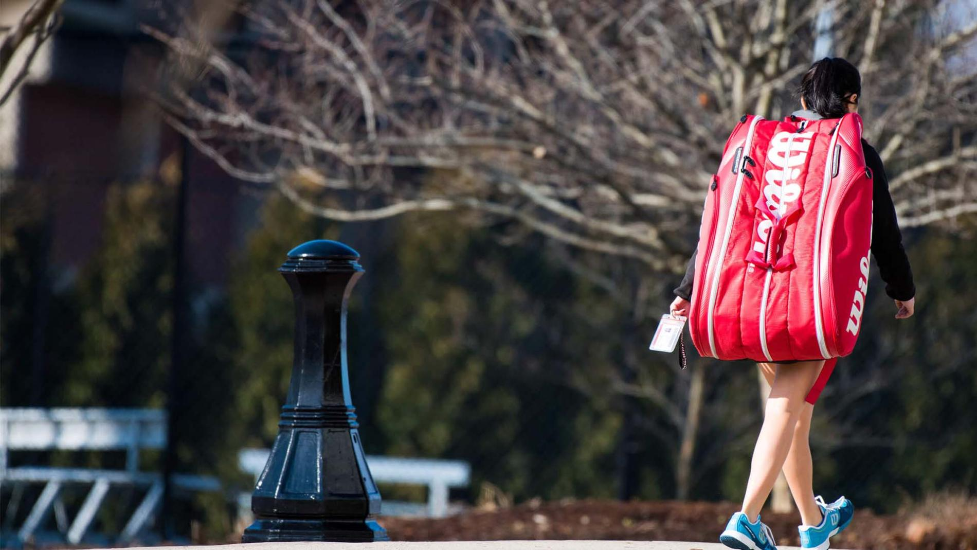 A student walks across the Springfield College campus while lugging a large sports bag on her back.