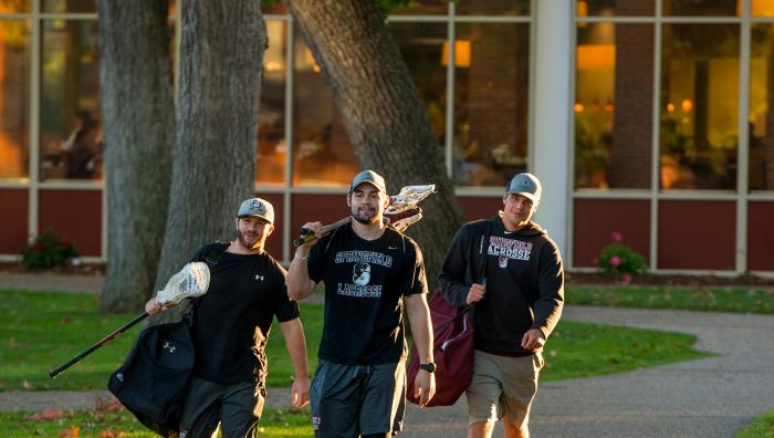 Students walking from lacrosse practice in the evening sun