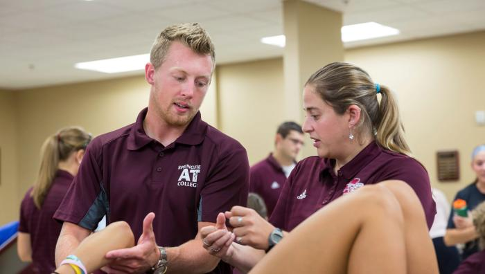 Two athletic training students working on a client's arm in an athletic training facility.