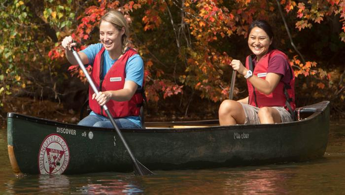 Students on a Canoe at Camp Massasoit, where you can find challenge courses, camps and more.