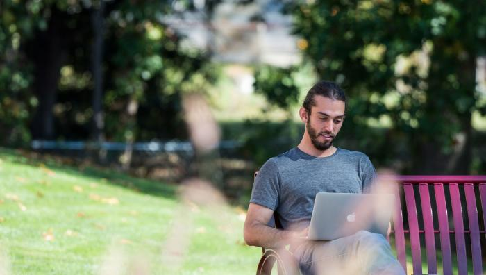 A student studies on his laptop outdoors on a bench.