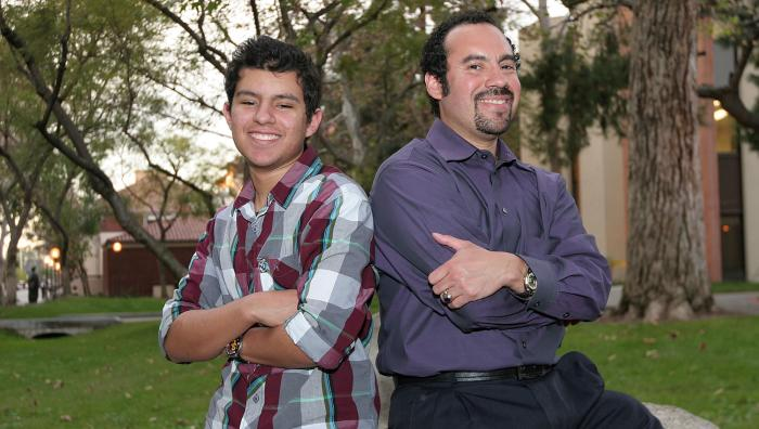 Graduate Miguel Trujillo '05 poses with youth outdoors