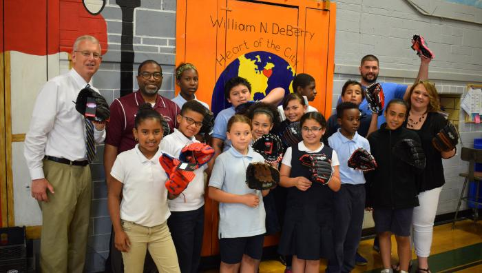 Office of Inclusion delivers baseball gloves to children in the community.