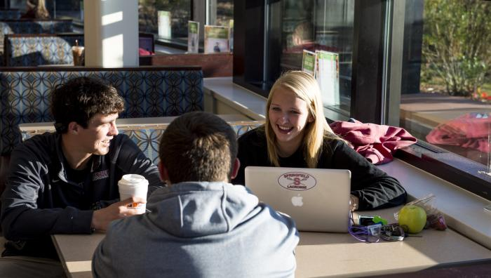 Students sit in the campus union and laugh while looking at a laptop