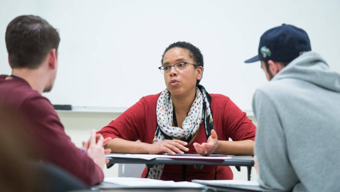 Professor discusses with two students in a classroom