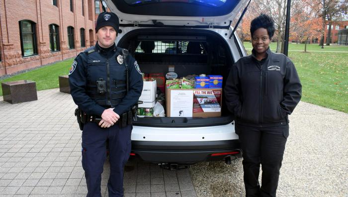 Officers of Public Safety stand by their police car filled with donations for a food drive
