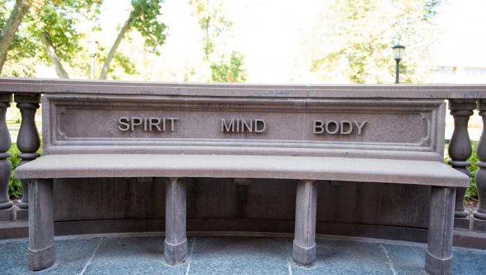 Spirit, Mind, and Body engraved on a bench on campus