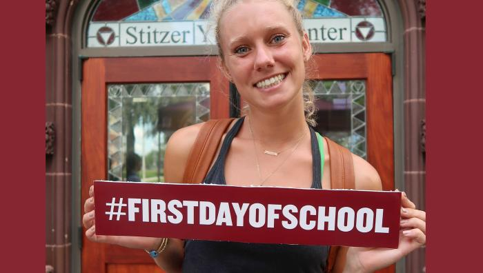 YMCA student posing with sign that says #FirstDayOfSchool