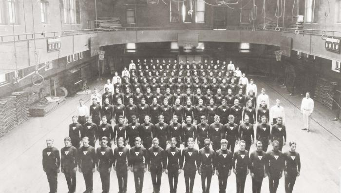 Old photo of YMCA men standing in gymnasium