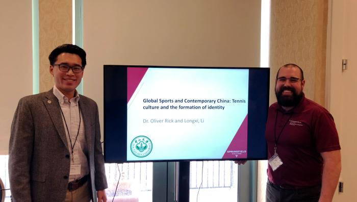 Doctoral student Longxi Li and Dr. Oliver Rick present their research at a conference