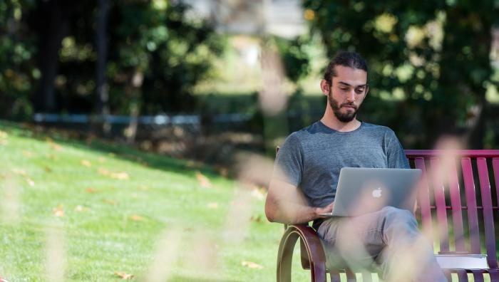 Student sitting on bench outside using a laptop