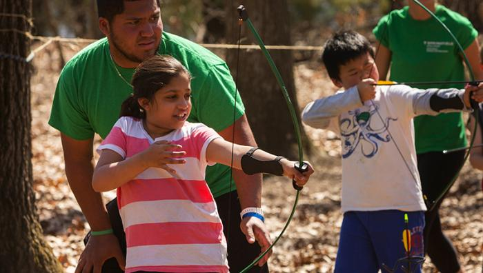 Students teaching children to shot bow and arrows