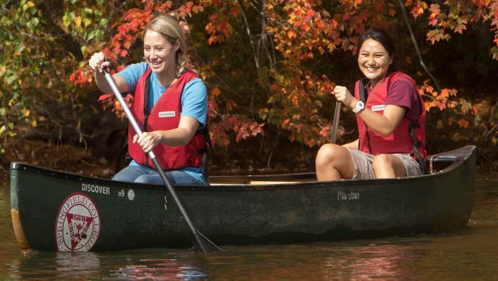 Two students in a canoe on Lake Massasoit