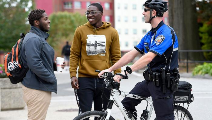 An officer on a bicycle has a discussion with two students