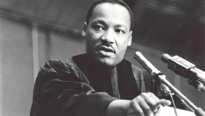 Photograph of Martin Luther King, Jr., taken on June, 1964 at Springfield College. Standing at the podium, King is looking to the camera's left, dressed in a graduation robe and in the middle of delivering the commencement speech.